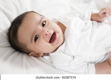 Adorable little baby girl laying in the bed. Little baby girl smiling and looking at the camera