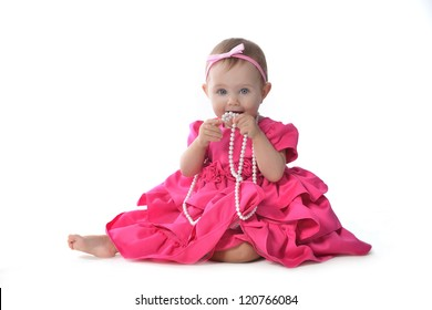 Adorable little baby girl  in  pink dress sitting on floor