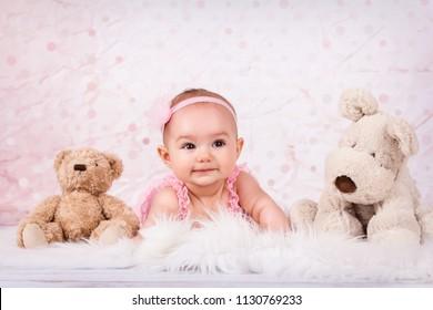 Adorable little baby girl smiling among plush toys