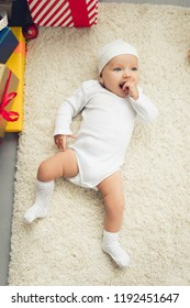 adorable little baby lying on floor with gift boxes