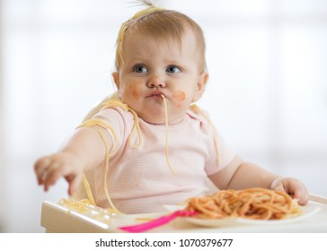 Adorable little baby one year old eating pasta indoor. Funny toddler child with spaghetti. Cute kid and healthy food.