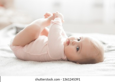 Adorable little baby portrait. Cute baby girl indoor. 6 month child smiling.