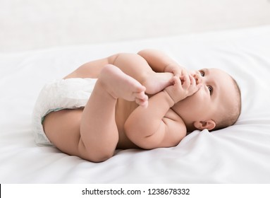 Adorable little baby sucking foot, lying on bed in diaper, white background
