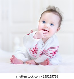 Adorable little baby wearing a knitted sweater with red Christmas ornament