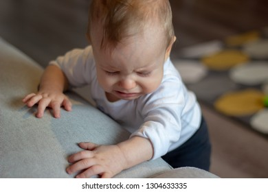 adorable little babyboy is standing holding the grey sofa with his two little hands with sad face eyes closed and starts to cry
