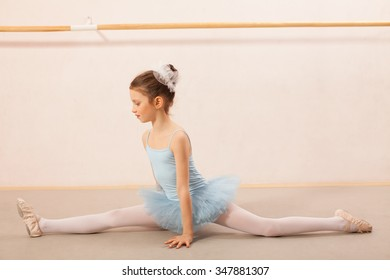 Adorable little ballerina dancer doing the splits pose in ballet studio. She is wearing blue leotard and tutu.