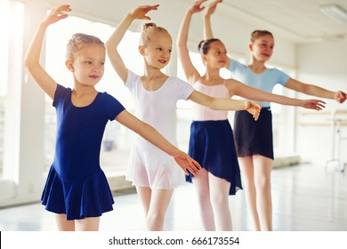 Adorable little ballerinas standing with hands up and exercising in class.