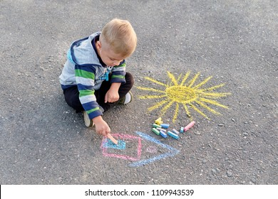 Adorable little blond boy drawing chalk outdoors. Outside activities for children. Child kid siting on asphalt sidewalk summer day, drawing house and sun painted by colored chalk. top view.