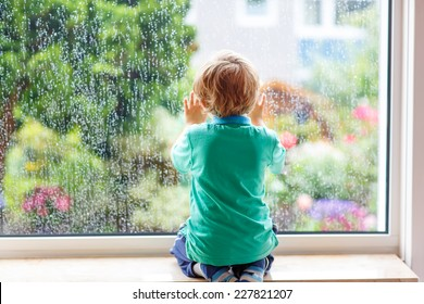 Adorable little blond child sitting near window and looking on raindrops, indoors.