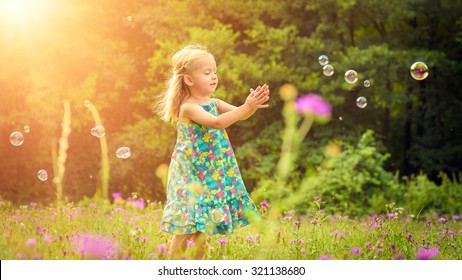 Adorable little blond girl having fun playing with soap bubbles during sunny summer afternoon
