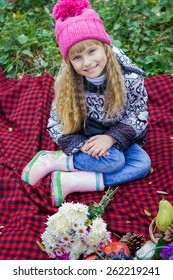Adorable little blond girl with long blond hair in autumn park. Beautiful little young baby in a pink hat. Beautiful child sitting on a red plaid.