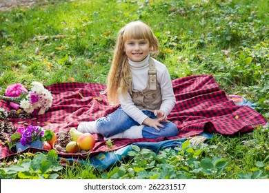 Adorable little blond girl with long blond hair in autumn park. Beautiful little young baby sitting  on a red plaid.  Lovely  child smiling with bright flowers