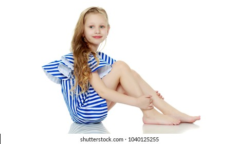 ef3c167e3dc Adorable little blond girl in very short summer striped dress.She sits on  the floor