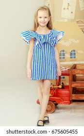 Adorable little blond girl in very short summer striped dress.It stands near a cardboard house and a wooden toy car.