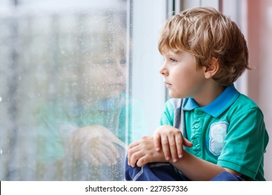 Adorable little blond kid boy sitting near window and looking on raindrops, indoors.