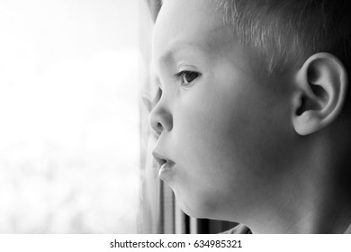 Adorable little blond kid boy sitting near window, baby