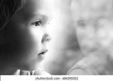 Adorable little blond kid boy sitting near window,black and white