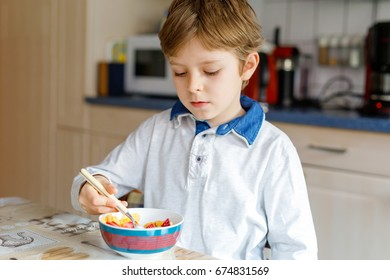 Adorable little blond school kid boy eating cereals with milk and berries, fresh strawberry for breakfast or lunch.