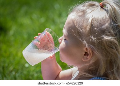 Adorable little blonde girl drinking lemonade with eyes closed on a hot sunny day