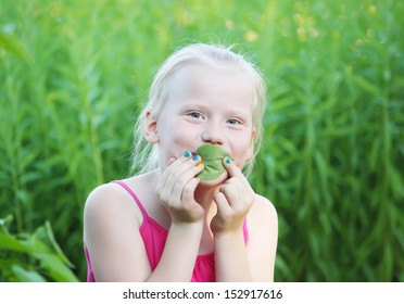 Adorable little blonde girl playing with green plant leaf in summer park.