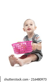 Adorable  little boy at the age of two in a striped T-shirt  looking up sitting and holding a pink basket with the ball on a white background