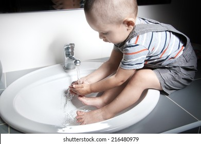 Adorable  little boy at the age of two in a striped T-shirt  looking at the flow of water in the sink and washing her hands and feet in the sink