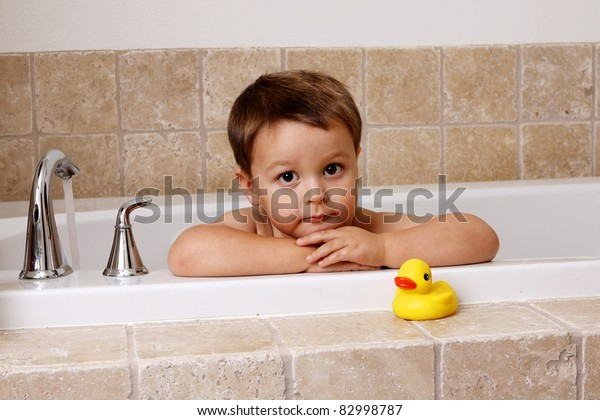 adorable little boy in bathtub with his rubber ducky