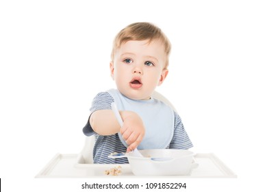 adorable little boy in bib sitting in highchair and eating by spoon isolated on white background
