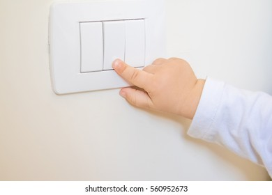 adorable little boy child turning on the white light-switch with his finger of little hand