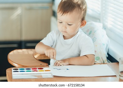Adorable little boy in a children's chair, draws and paints on paper