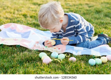 adorable little boy coloring easter eggs in the park