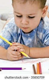 adorable little boy drawing whit colored pencil