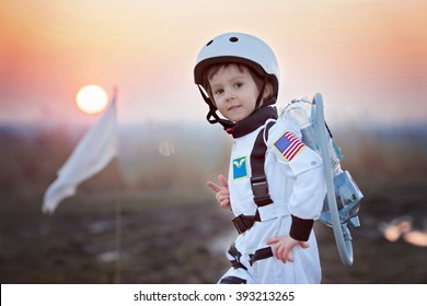 Adorable little boy, dressed as astronaut, playing in the park with rocket and flag, dreaming about becoming an astronaut