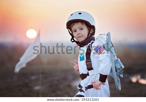 Adorable kleine Junge, verkleidet als Astronaut, spielend mit Rakete und Fahne, träumt davon, Astronautin zu werden