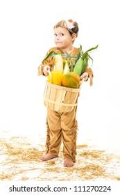 adorable little boy dressed as a Native American holding a basket of harvest vegetables