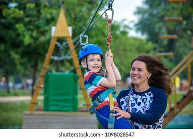 Adorable little boy enjoying his time in a rope playground structure at adventure park, his mother giving a helping hand to him, family weekend activities, spring outdoor
