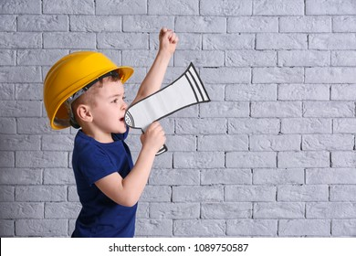 Adorable little boy in hardhat with paper megaphone on brick wall background