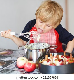 Adorable little boy helping and baking apple pie in home''s kitchen, indoor. Tasting vanilla dough.