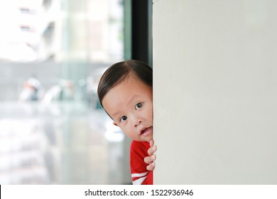 Adorable little boy hide behind a corner room. Baby playing peekaboo game indoor.