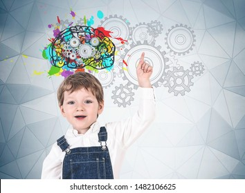 Adorable little boy in jeans overalls pointing up standing near gray wall with colorful brain sketch, cogs and gears. Concept of creative thinking, education and brainstorming