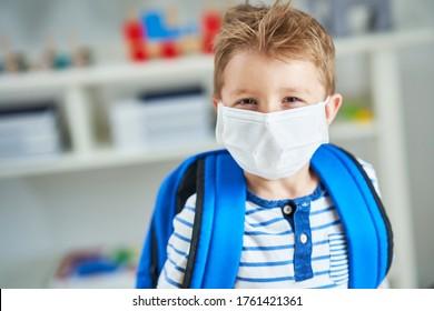 Adorable little boy in kindergarten with mask on due to coronavirus pandemic - Shutterstock ID 1761421361