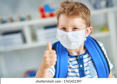 Adorable little boy in kindergarten with mask on due to coronavirus pandemic - Shutterstock ID 1761421397
