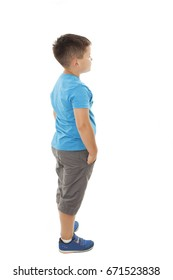 Adorable little boy looking at wall. Isolated on white background