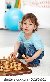 Adorable little boy playing with chess pieces indoors