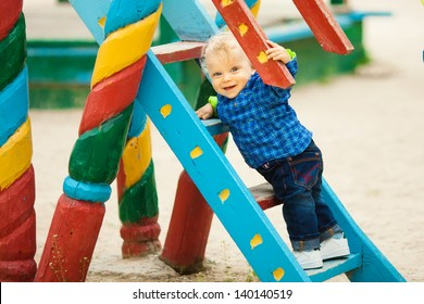 Adorable little boy playing on playground at park.