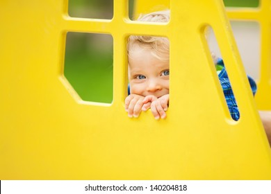 Adorable little boy playing on playground at park. Soft focus on eyes.