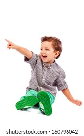 Adorable little boy pointing at something isolated on white background