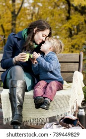 Adorable little boy  reaches for his mother's kiss with cup of ginger tea on wooden bench in park