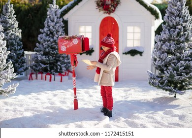 Adorable little boy with red hat and green glasses sending her letter to Santa, Christmas time