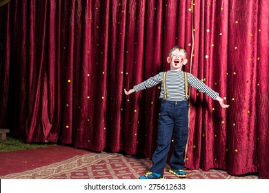 Adorable little boy singing on stage during a play standing with outstretched arms in his costume and makeup in front of the burgundy colored curtain